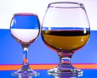 Um vidro da vodca e um vidro da aguardente, do uísque ou do bourbon em um branco ou em um fundo colorido Imagem de Stock Royalty Free