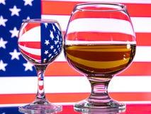 Um vidro da vodca e um vidro da aguardente, do uísque ou do bourbon em um branco ou em um fundo colorido Imagens de Stock Royalty Free