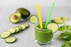 Um vidro de batidos vegetais verdes em um fundo de madeira branco Imagem de Stock