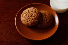 Um vidro de cookies frescas do leite e de farinha de aveia em uma tabela de madeira Foto de Stock