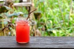 Um vidro de refrescos frutados tropicais congelados em uma prancha velha foto de stock royalty free