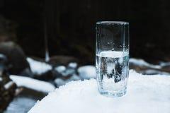 Um vidro de vidro transparente com água bebendo da montanha está na neve contra um fundo de uma montanha limpa da geada Foto de Stock