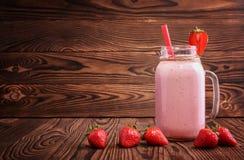 Um vidro de uma bebida cor-de-rosa brilhante das morangos frescas e as bagas estão ao redor Bebida saudável da morango em um fund Imagem de Stock Royalty Free