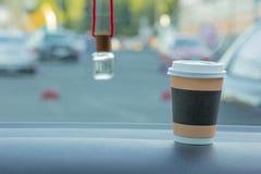 Um vidro do café, em um fundo obscuro de um refrogerador de ar do carro imagens de stock