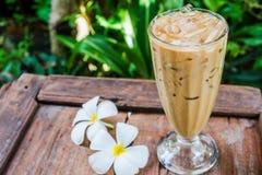 Um vidro do café no jardim com plumeria branco floresce na madeira foto de stock royalty free