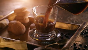 Um vidro do café preto úmido quente em uma bandeja do metal, estando em uma tabela de madeira, cercada por feijões de café filme
