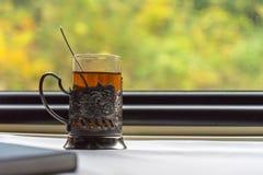 Um vidro do chá no vidro-suporte, na tabela no trem imagens de stock