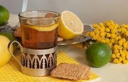 Um vidro do chá preto em um suporte de vidro, alguns biscoitos, os limões maduros e os cais em um linho surgem contra o fundo cla Foto de Stock