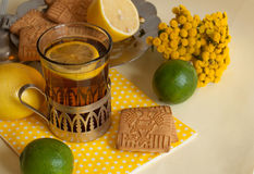 Um vidro do chá preto em um suporte de vidro, alguns biscoitos, os limões maduros e os cais em um linho surgem contra o fundo cla Fotografia de Stock