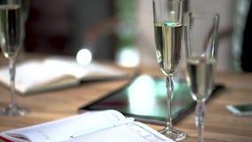 Um vidro do champanhe e de um diário no desktop no gerente na sala de conferências vídeos de arquivo