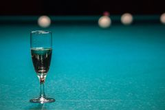 Um vidro do champanhe está na mesa de bilhar o vencedor do jogo, o campeão bebe um vidro do vinho espumante Passatempos, esportes foto de stock