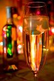 Um vidro do champanhe no fundo das luzes Imagens de Stock Royalty Free
