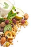 Um vidro do leite e do muesli com frutos e ervas em um fundo branco Isolado imagem de stock royalty free