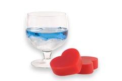 Um vidro do licor com dois corações. Imagem de Stock