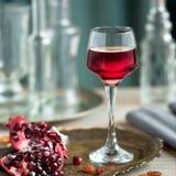 Um vidro do licor da romã na tabela com granadas imagem de stock royalty free