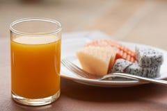 Um vidro do suco de laranja e de uma placa dos frutos na tabela fotografia de stock royalty free