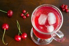 Um vidro do suco vermelho da cereja com cubos de gelo e cerejas e corintos vermelhos em um close up de madeira do fundo Foto de Stock