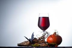 Um vidro do vinho com as decorações para Dia das Bruxas na tabela Fotos de Stock Royalty Free