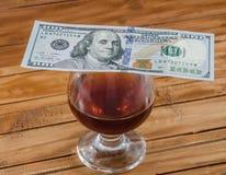 Um vidro do vinho e dos dólares em um vidro fotografia de stock royalty free