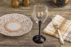 Um vidro do vinho em uma tabela de madeira do fundo, com uma placa com uma forquilha Uma garrafa do vinho e dos acessórios Fotografia de Stock