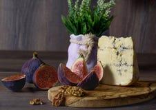 Um vidro do vinho tinto com os petiscos do queijo, das uvas dos figos e do NU fotografia de stock royalty free