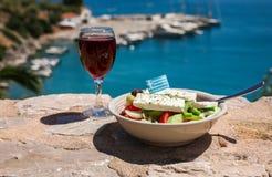 Um vidro do vinho tinto e da bacia da salada grega com bandeira grega sobre pela opinião do mar, conceito grego dos feriados do v Fotos de Stock Royalty Free