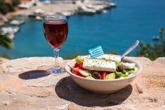 Um vidro do vinho tinto e da bacia da salada grega com bandeira grega sobre pela opinião do mar, conceito grego dos feriados do v Fotografia de Stock Royalty Free