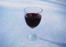 Um vidro do vinho tinto em um fundo branco Um vidro do vinho na neve branca Imagens de Stock