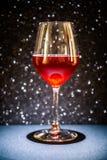 Um vidro do vinho tinto, o fundo é efervescente preto, o tanque é iluminado com uma luz direcional de cima de foto de stock royalty free