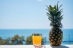 Um vidro enchido com o suco contra o contexto do mar Fruta fresca do abacaxi Alimento saudável foto de stock royalty free