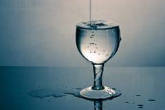 Um vidro enchido em demasia com água Fotos de Stock Royalty Free
