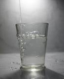 Um vidro está enchendo-se com água Fotos de Stock Royalty Free