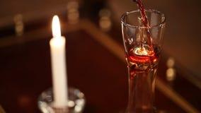 Um vinho tinto de derramamento do sommelier no filtro filme