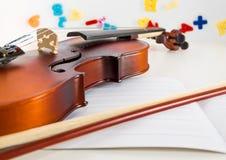 Um violino e uma curva pequenos do ` s das crianças em um ` s da criança estudam a mesa fotografia de stock