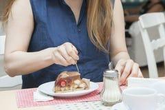 Um visitante a um café está comendo as mãos de uma sobremesa, dispositivos, servindo fotos de stock royalty free