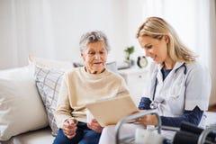 Um visitante da saúde e uma mulher superior que sentam-se em uma cama em casa, falando imagem de stock