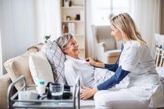 Um visitante da saúde que examina uma mulher superior doente que encontra-se na cama em casa com estetoscópio fotos de stock royalty free