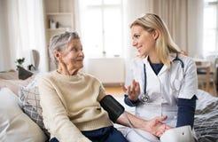 Um visitante da saúde que mede uma pressão sanguínea de uma mulher superior em casa fotos de stock royalty free