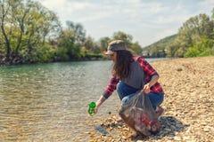 Um volunt?rio da mulher puxa uma garrafa fora da ?gua, durante o evento para limpar o banco de rio Dia da Terra e ambiental imagem de stock royalty free