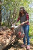Um volunt?rio do estudante limpa uma ?rea da floresta do lixo O conceito do voluntarismo e da prote??o ambiental fotografia de stock
