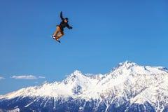 Um voo masculino do cavaleiro do snowboard de um salto de esqui no fundo nevado da montanha Fotos de Stock