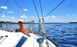 Um 'yachtsman' que ruddering um barco Foto de Stock