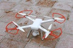 Um zangão do quadrocopter está na neve em uma telha vermelho-marrom pronto para voar no inverno foto de stock