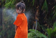 Uma água do respingo da menina no jardim Imagem de Stock