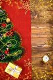 Uma árvore de Natal pequena do ouropel, das porcas, das fitas e dos ornamento Presente para uma árvore de Natal, um relógio do vi fotografia de stock royalty free