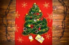 Uma árvore de Natal pequena do ouropel, das porcas, das fitas e dos ornamento Presente para uma árvore de Natal, um relógio do vi imagens de stock