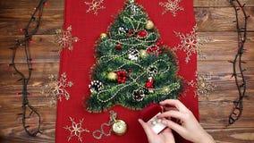 Uma árvore de Natal pequena do ouropel, das porcas, das fitas e dos ornamento Presente para uma árvore de Natal, um relógio do vi filme