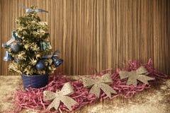 Uma árvore de Natal pequena em um fundo de madeira para cartão e Imagem de Stock
