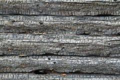 Uma árvore redonda, uma parede da madeira enegreceu pelo fogo Fundo imagens de stock