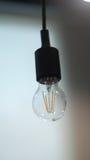 Uma única luz fora do pendurado abaixo da lâmpada no escritório Fotografia de Stock Royalty Free
